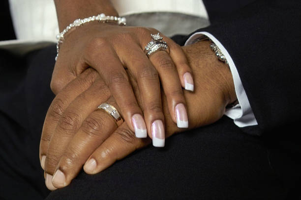 just married holding hands stock photo - African Wedding Rings