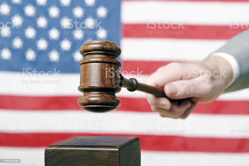 Justice! Wooden gavel strikes against background of Stars and Stripes royalty-free stock photo