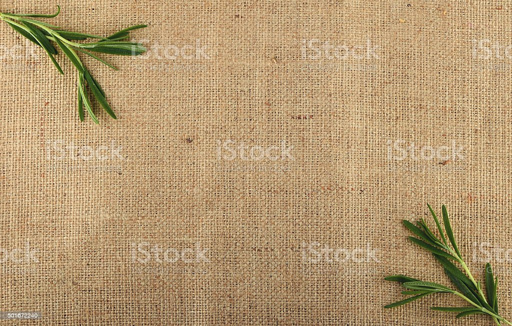 Jute canvas with rosemary leaves in corners royalty-free stock photo