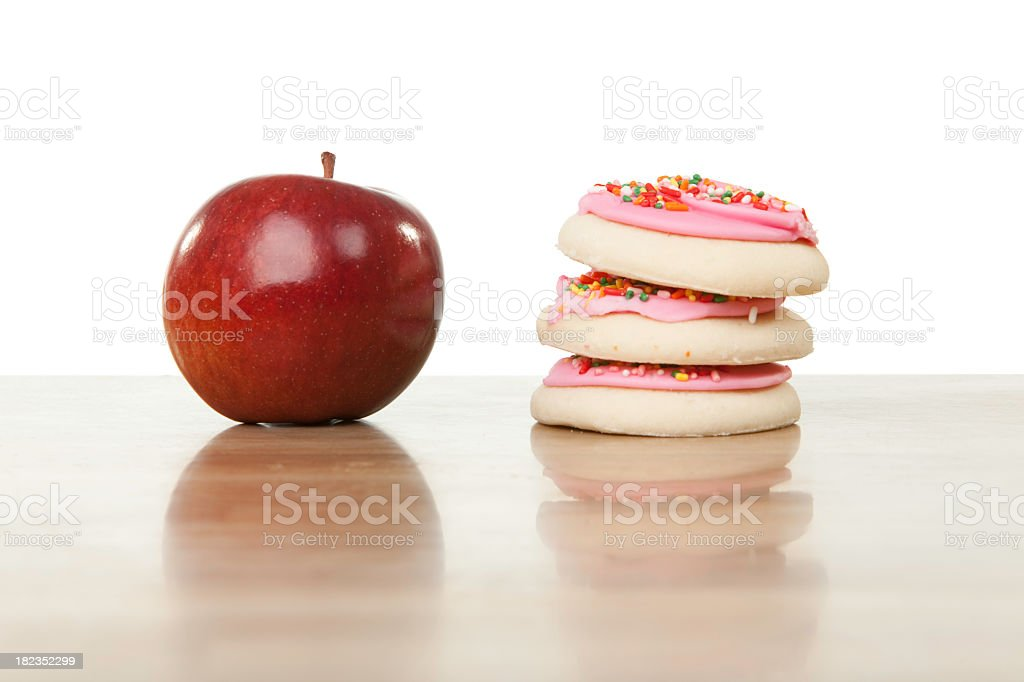 Juxtaposition of a healthy apple beside unhealthy cookies stock photo