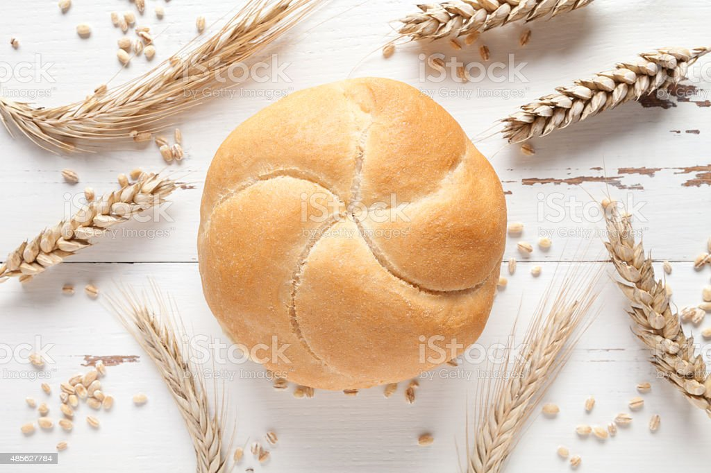 Kaiser roll and wheat ears on white table stock photo