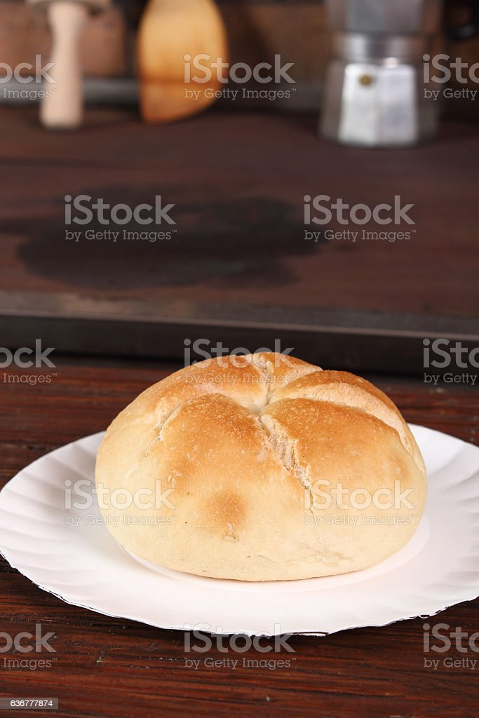 Kaiser roll on paper plate at rural kitchen background stock photo