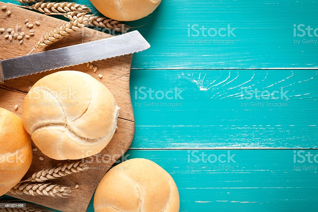 Kaiser rolls with knife and cutting board stock photo
