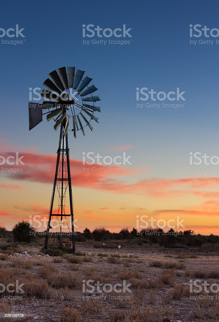 Kalahati sunset with trees grass windmill and blue sky stock photo