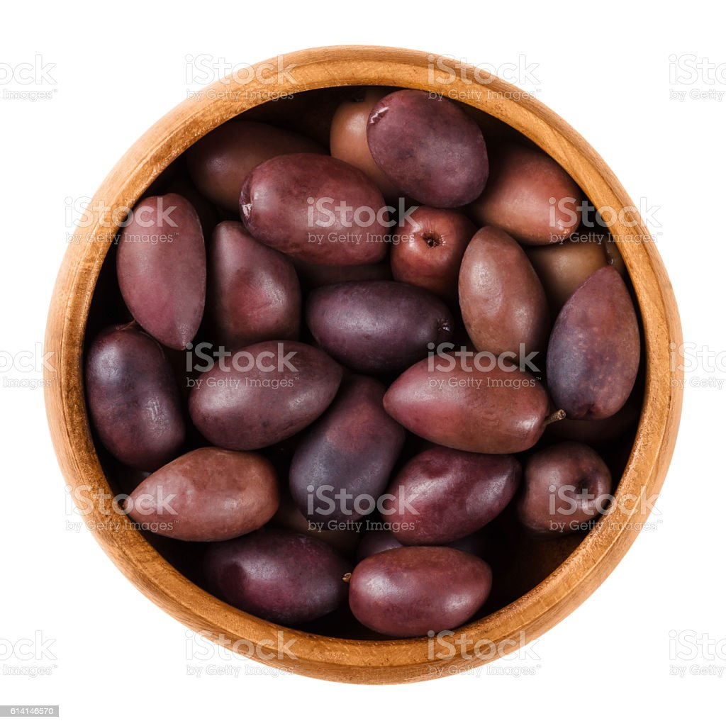 Kalamata black olives in a wooden bowl over white stock photo