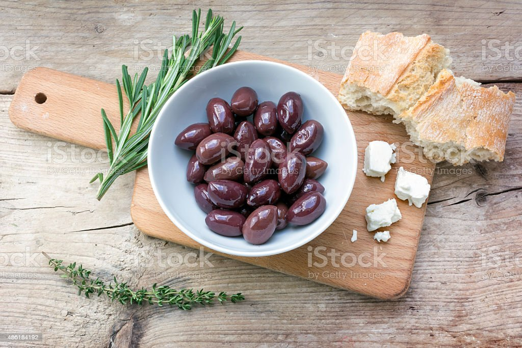 Kalamata olives, bread, feta cheese and herbs on rustic wood stock photo