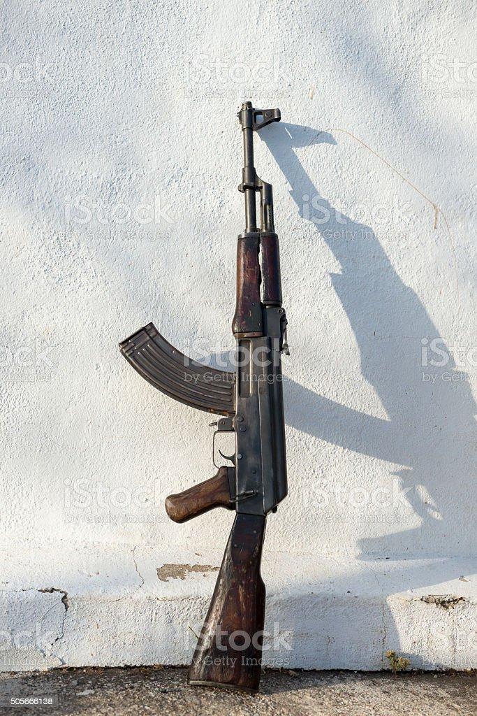 Kalashnikov AK-47 rifle leaned against wall stock photo