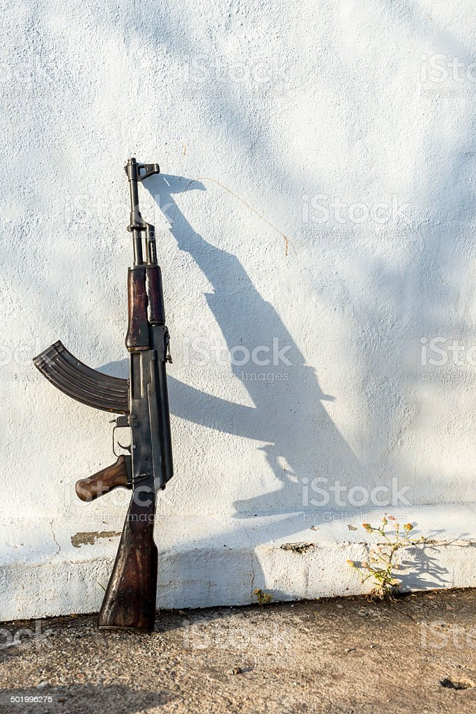 Kalashnikov rifle leaned against wall stock photo