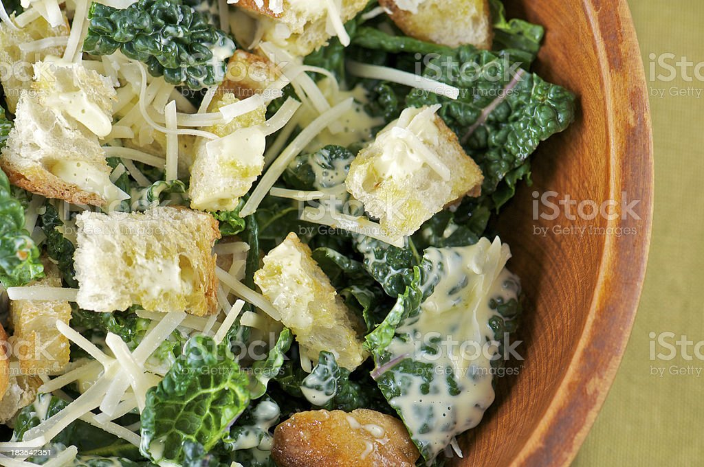 Kale Caesar Salad in Wooden Bowl from Above stock photo
