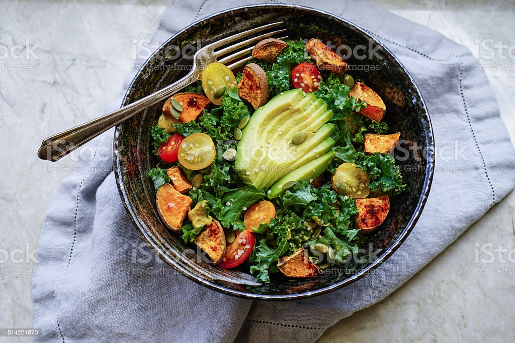 Kale, roasted yams and avocado salad stock photo