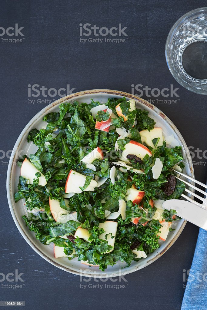 Kale salad with apples, almond slices and raisins. Selective focus stock photo
