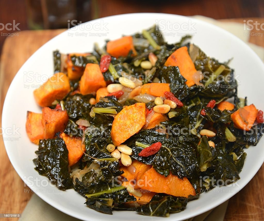 Kale with baked Veggies on white plate royalty-free stock photo
