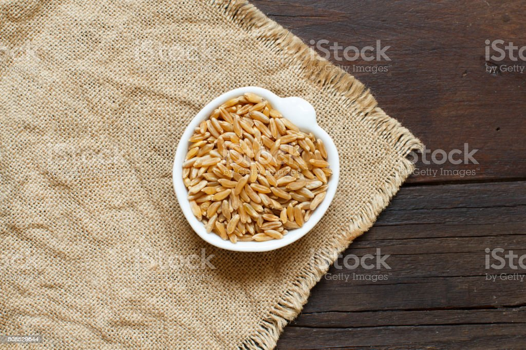 Kamut grain on wooden background stock photo