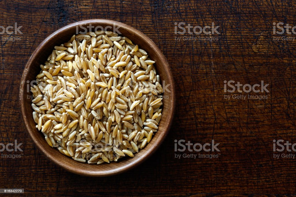 Kamut wheat kernels in dark wooden bowl isolated on dark brown wood from above. stock photo