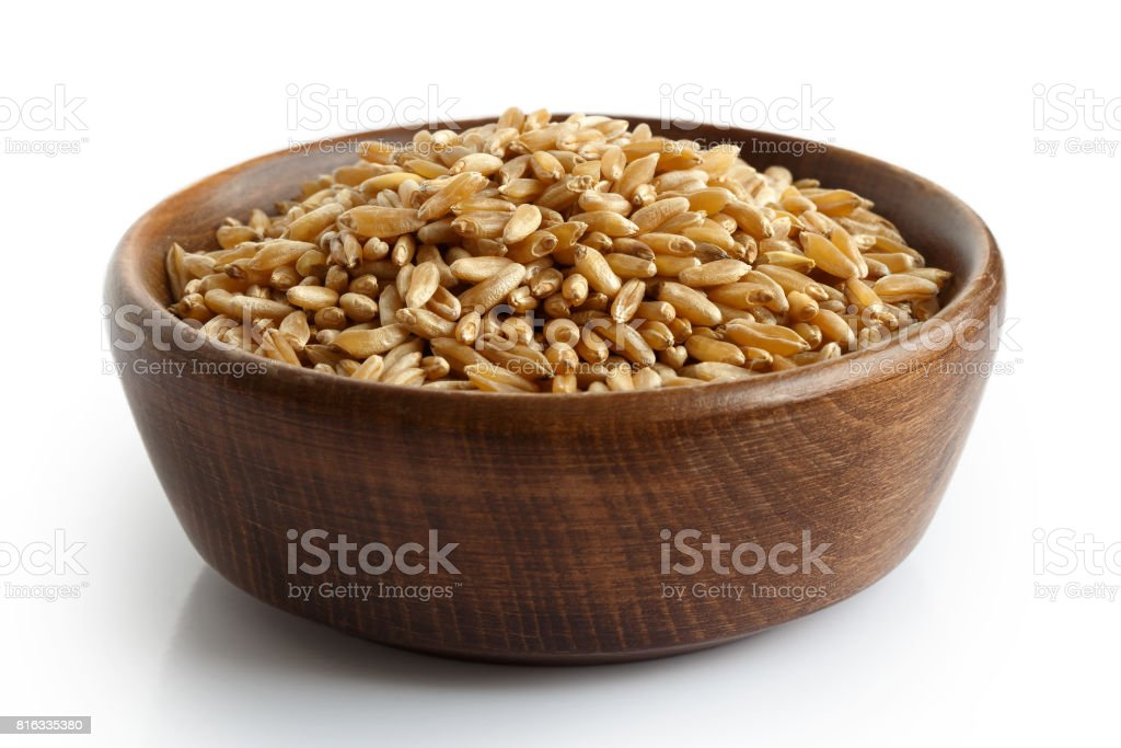 Kamut wheat kernels in dark wooden bowl isolated on white. stock photo