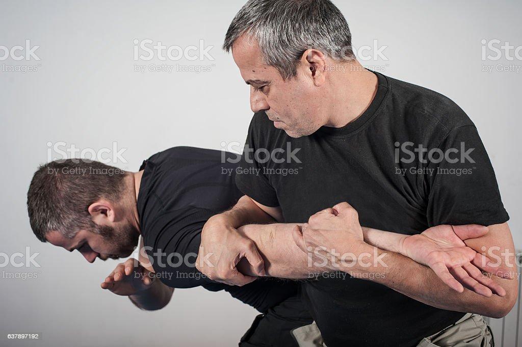 Kapap instructor demonstrates arm bar techniques stock photo