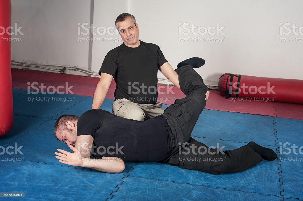 Kapap instructor demonstrates ground fighting techniques stock photo