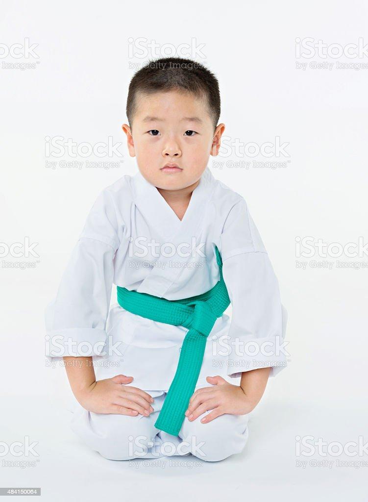 Karate boy sitting on floor stock photo