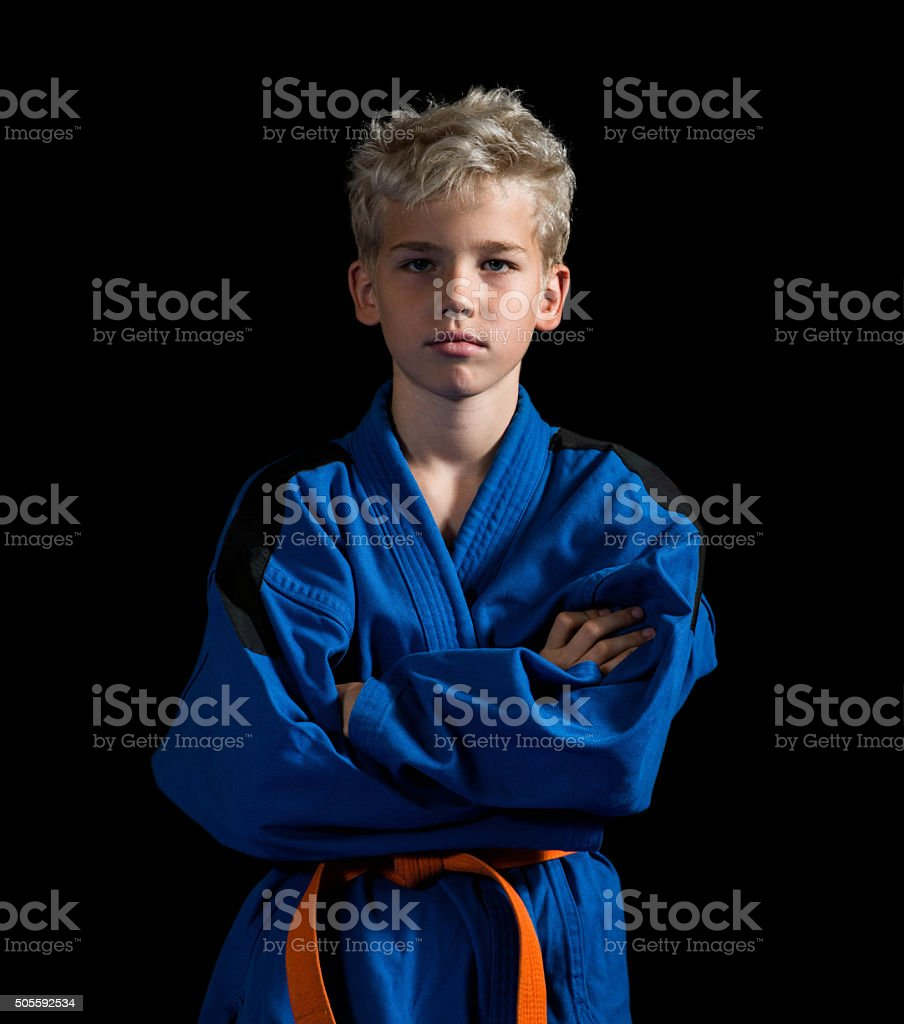 Karate boy with arms crossed looking at camera. stock photo