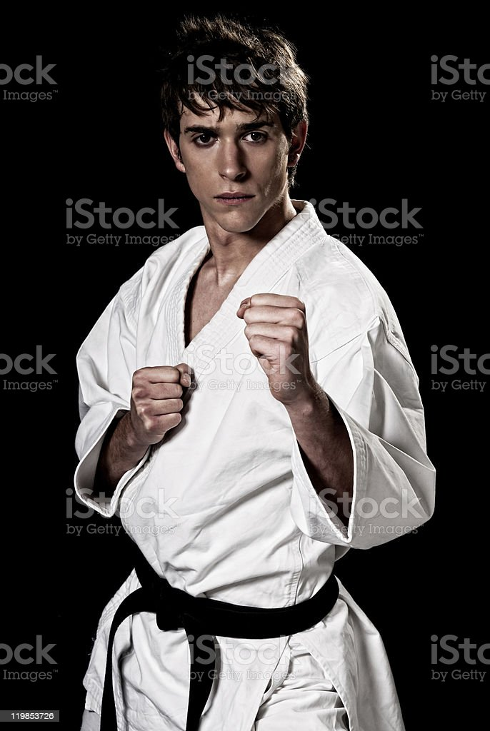 Karate male fighter young high contrast on black background.
