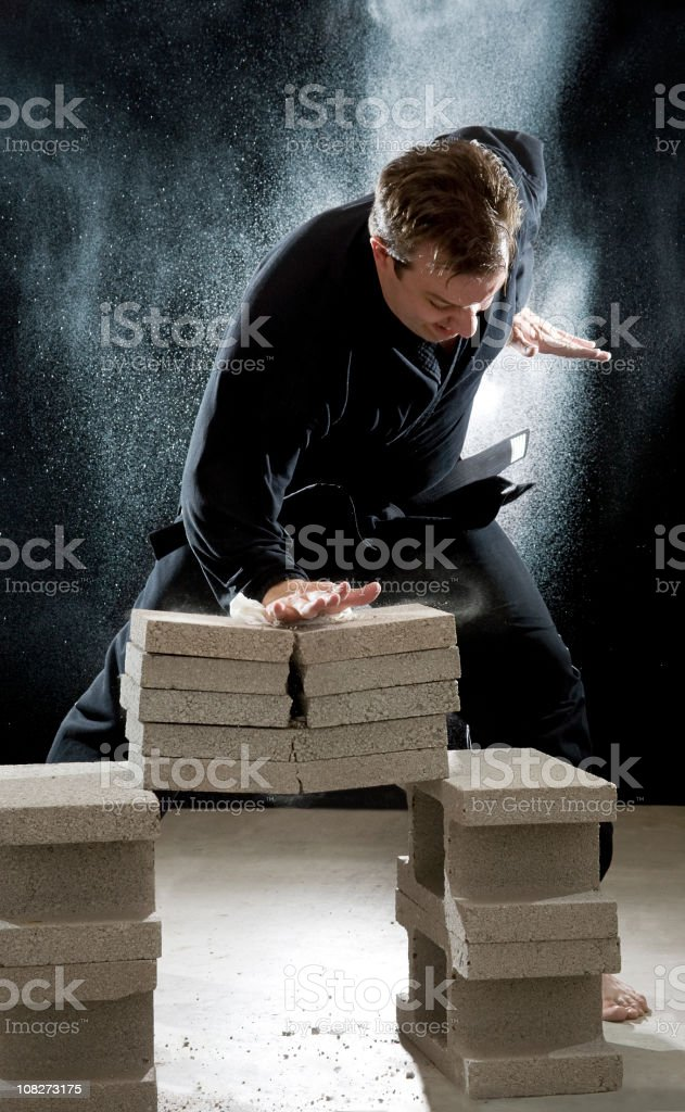 Karate Man Breaking Cinder Blocks stock photo
