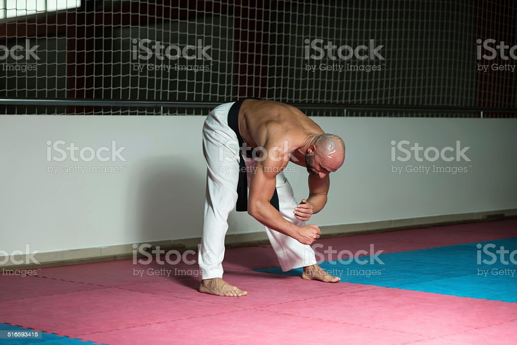 Male Martial Arts Instructor Preparing For Class - Warming Up and...