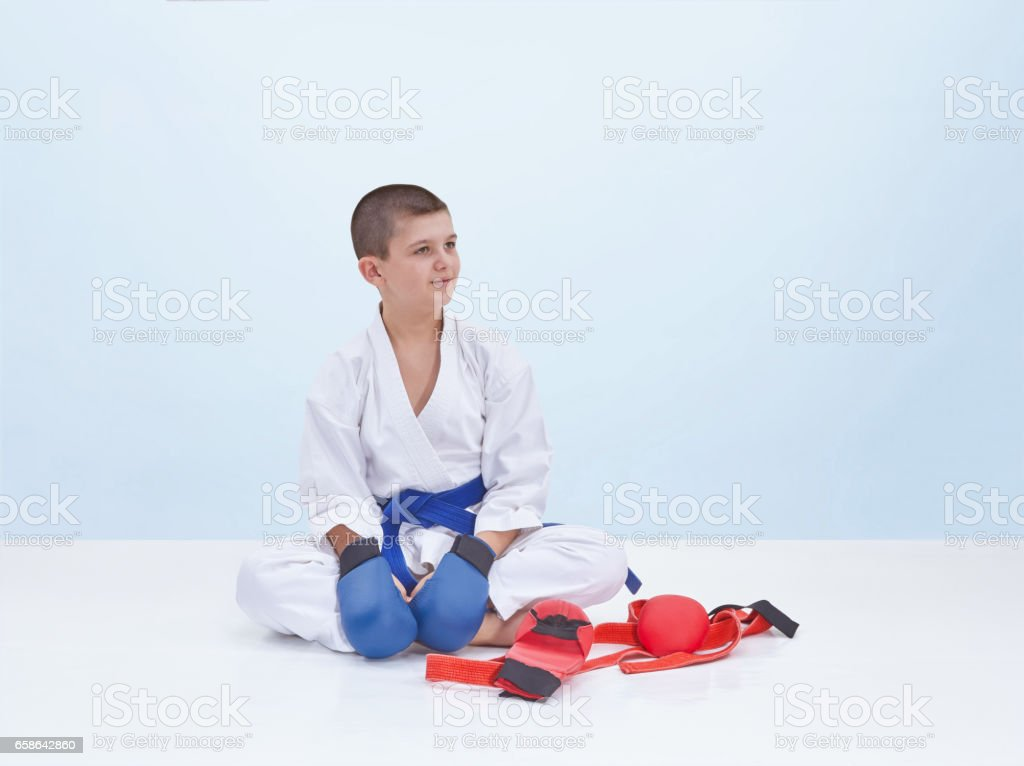 Karate sportsman sits near a karate outfit stock photo