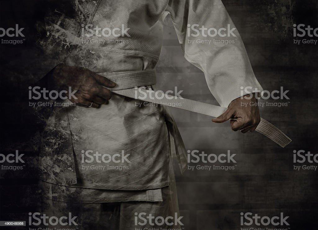 Karateka tying the white belt (obi) with grunge background stock photo
