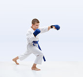 Karateka with blue overlays on hands is beating punch