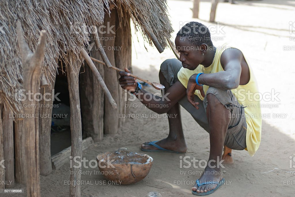 Karo man has traditional breakfast, sorghum cereal, in Colcho, Ethiopia. stock photo