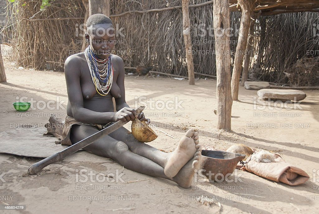 Karo woman peels calabash in Colcho, Omo Valley, Ethiopia. stock photo