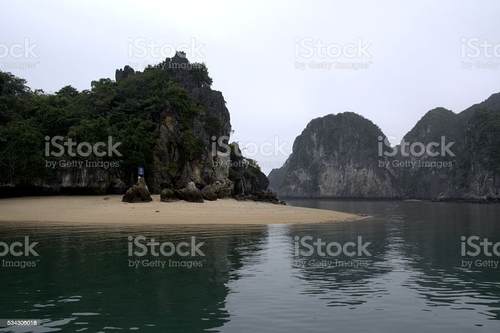 Karst island with sandy beach in Lan Ha bay, Vietnam stock photo