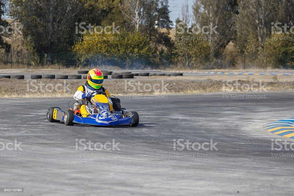 Karting - driver in helmet on kart circuit stock photo