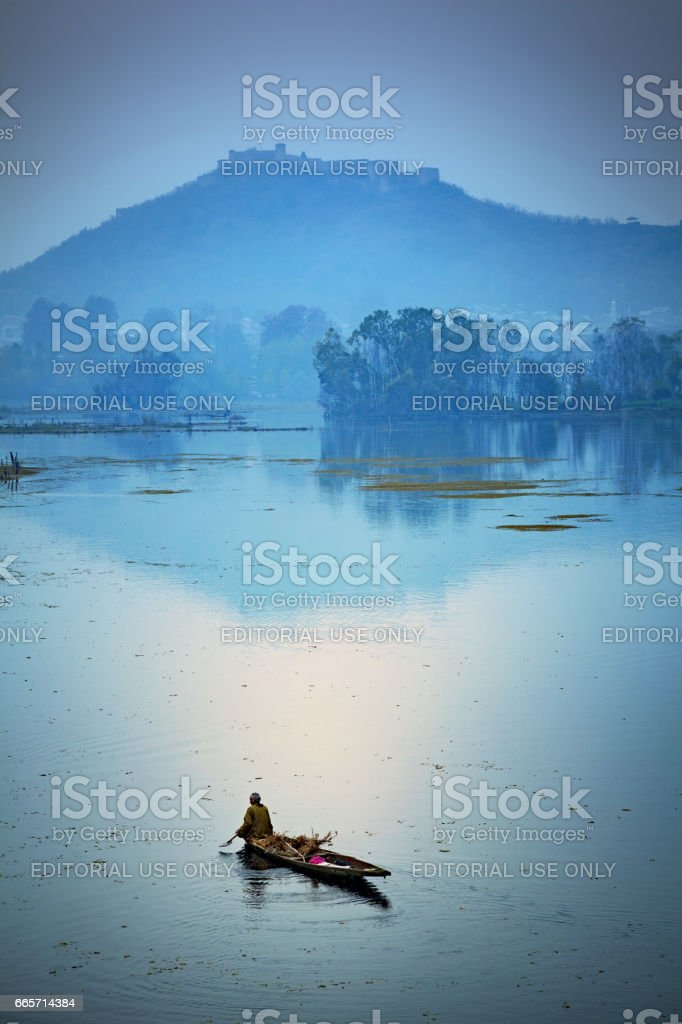 A Kashmiri man rowing his canoe, also seen a fort on a hill-top at Nageen Lake stock photo