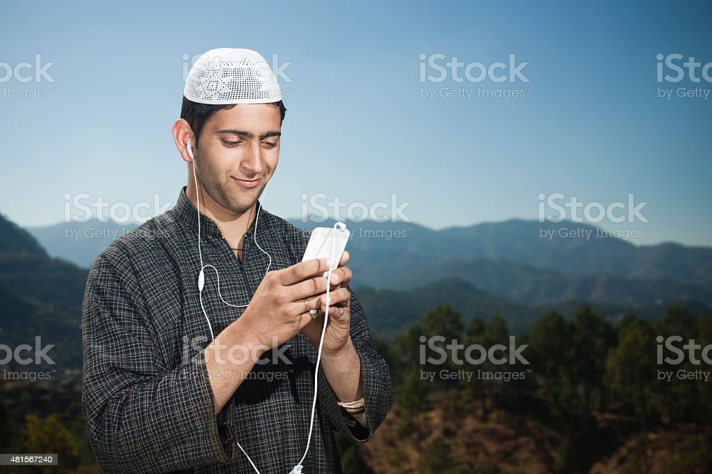 Kashmiri young man in mountains using phone with headphones on. stock photo