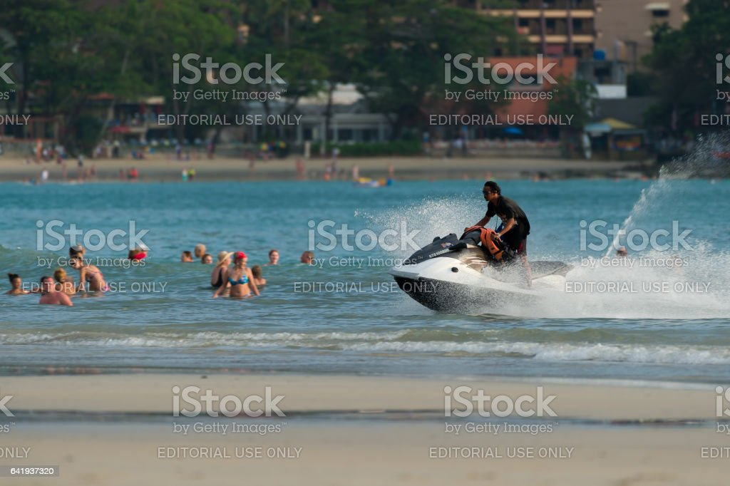 Kata beach,Phuket-November 17, 2016 :Time out for jet ski services. Beach boy riding jet ski watercraft for rent  back to the beach at sunset. stock photo
