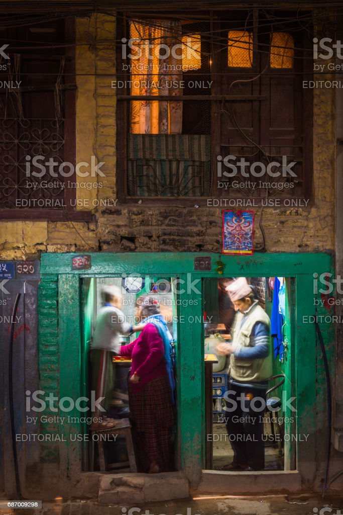 Kathmandu night Newar family in illuminated roadside restaurant Nepal stock photo