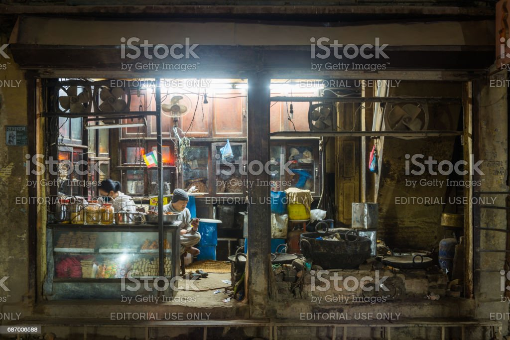 Kathmandu night shopkeepers waiting for customers in roadside kitchen Nepal stock photo