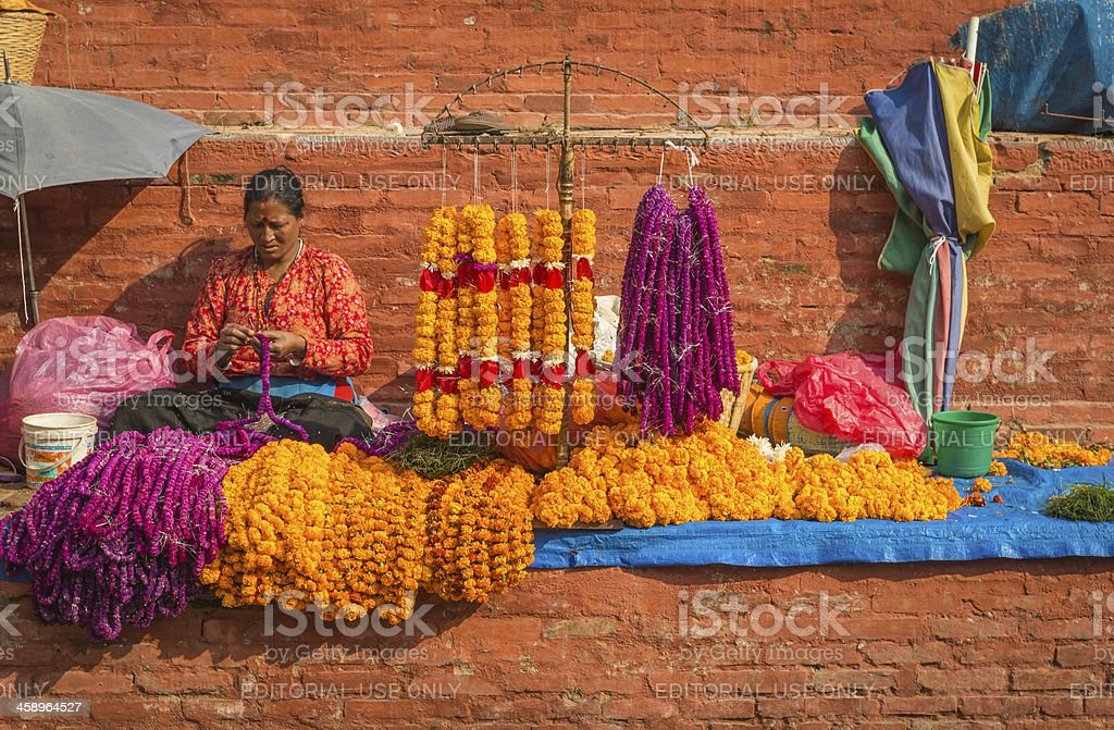 Kathmandu woman making flower garlands in Durbar Square Nepal stock photo