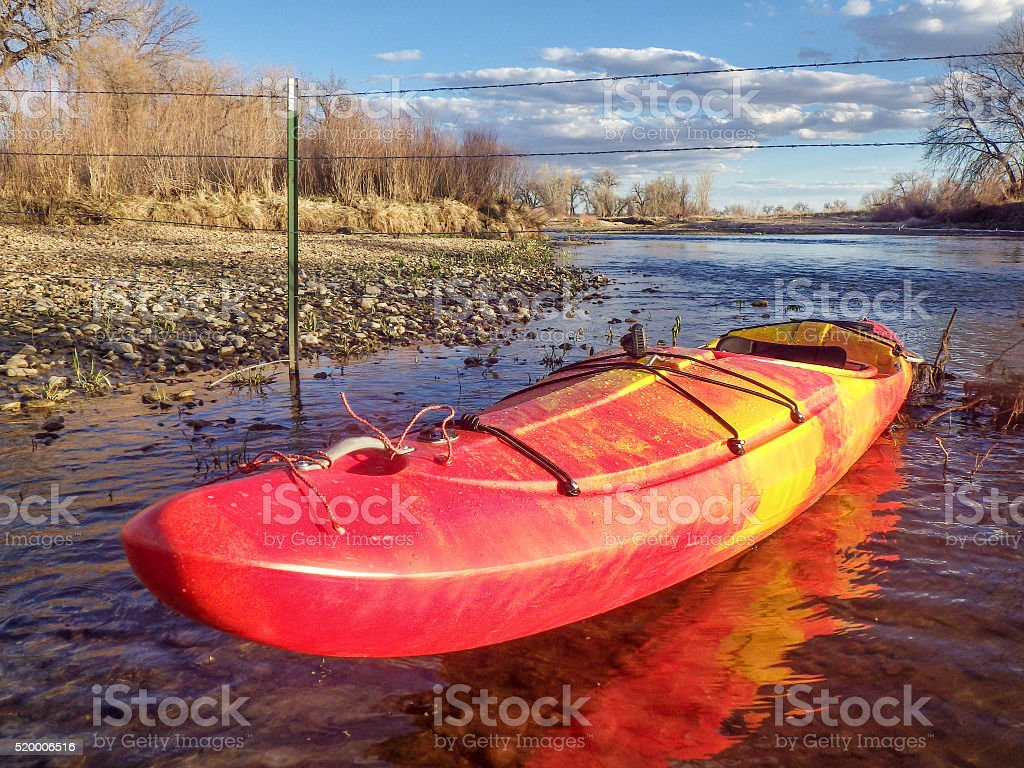 kayak and fence across river stock photo