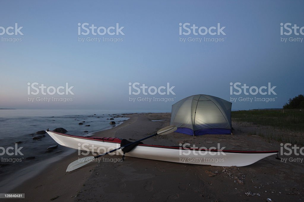 Kayak and Illuminated Tent On Beach at Night royalty-free stock photo