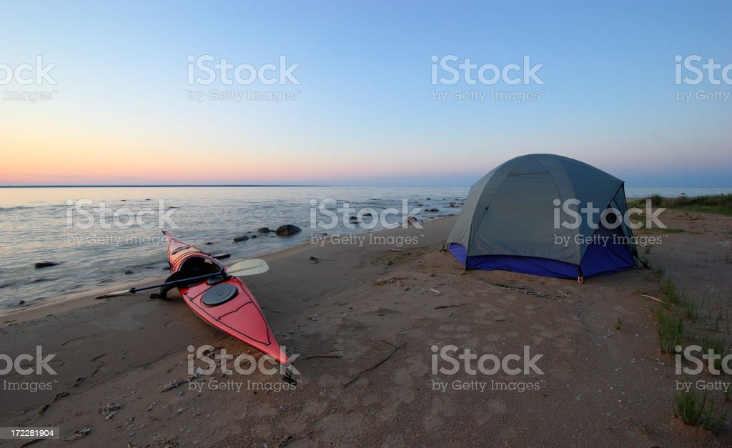 Kayak and Tent on Secluded Beach at Sunset royalty-free stock photo