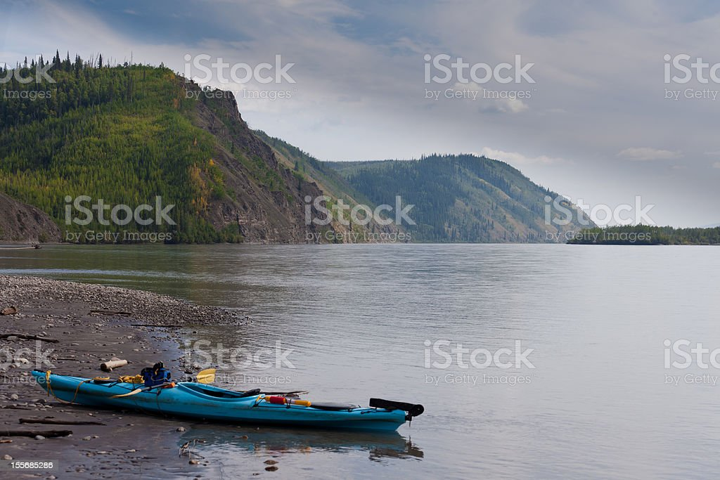Kayak beached on the shore of Yukon River Canada royalty-free stock photo