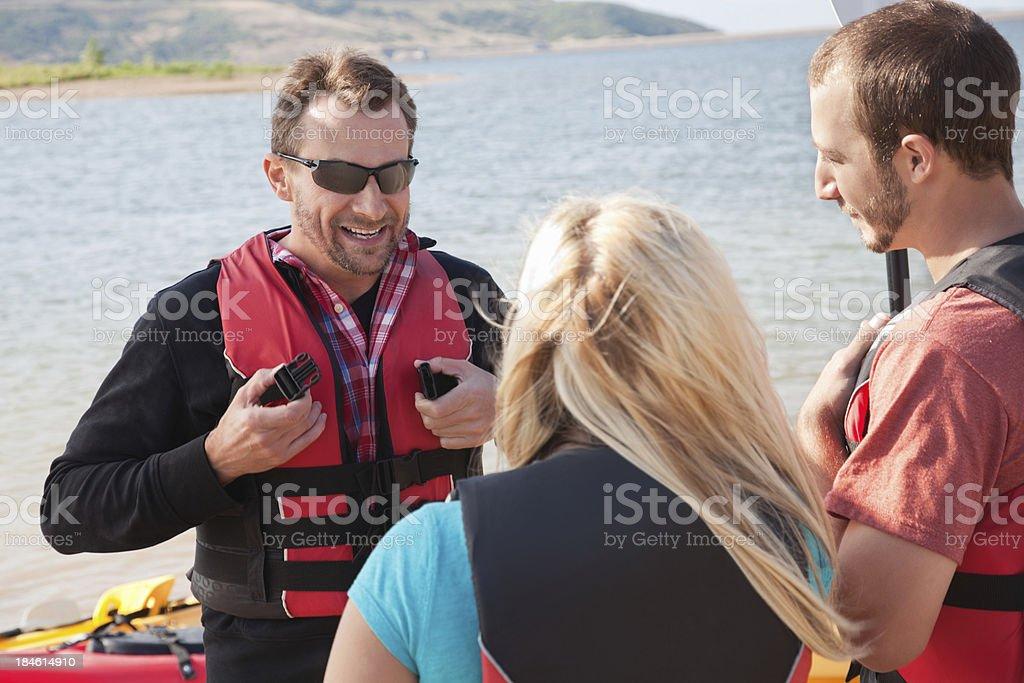 Kayak instructor explaining safety precautions to kayakers royalty-free stock photo