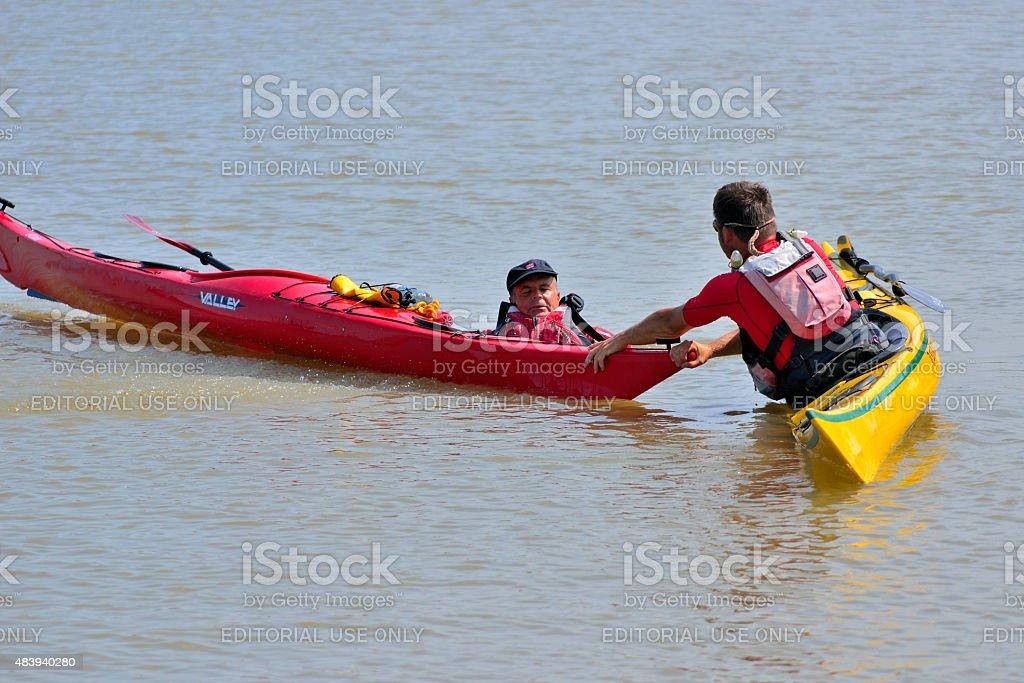 Kayak Instructor Thomas Aigner helps a capsized kayaker stock photo