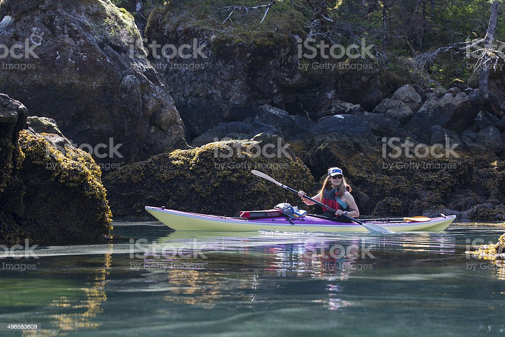 Kayaker among rocks in Humpy Cove stock photo