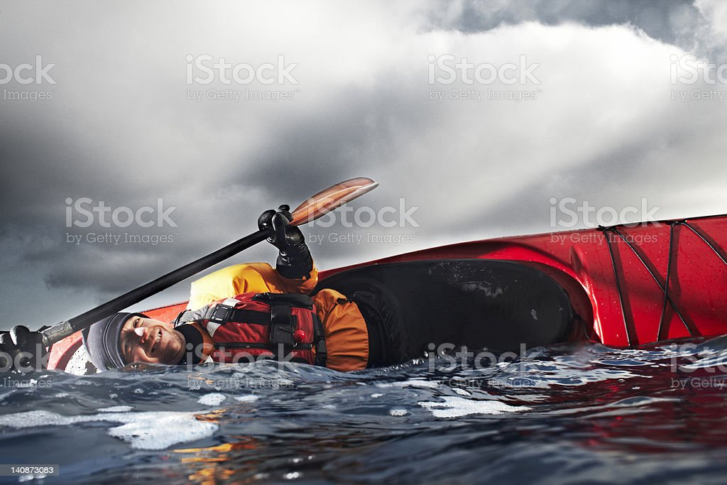 Kayaker flipped over in water stock photo