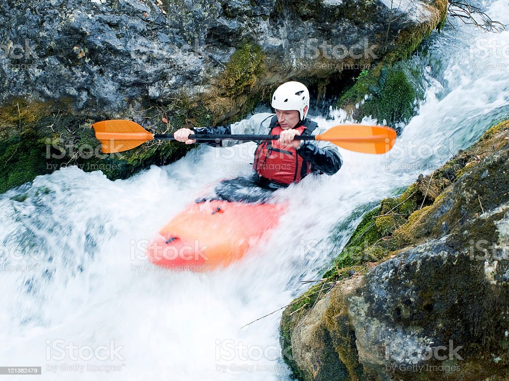 A kayaker going down a rapid in a rocky river stock photo