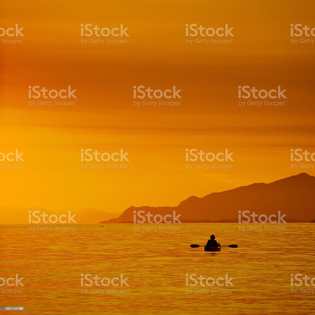 Kayaker in sunset. stock photo