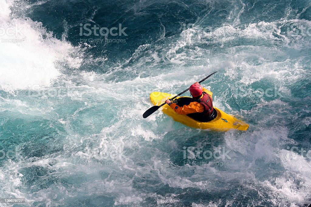 Kayaker maneuvers over rough waters  stock photo